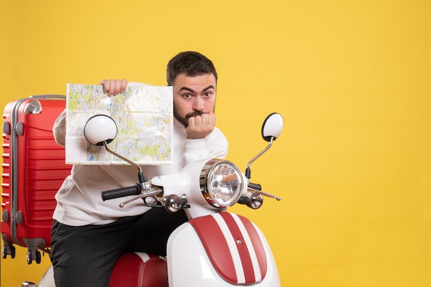 Front view of concentrated man sitting on motorcycle with suitcase on it holding map on isolated yellow background