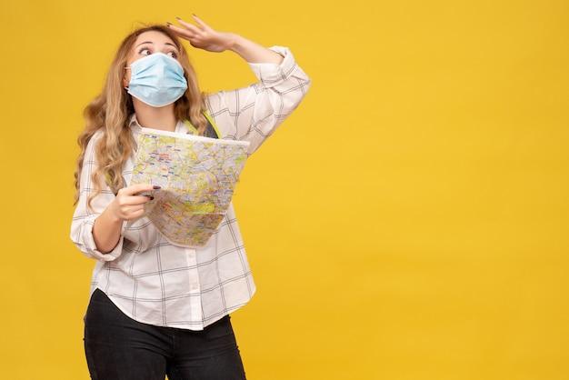 Vista frontale della ragazza di viaggio concentrata che indossa la sua mappa della tenuta dello zaino e della maschera sul giallo