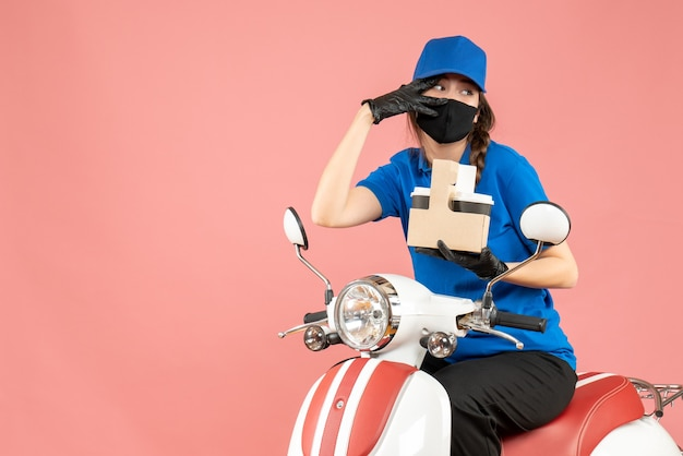 Front view of concerned female delivery person wearing medical mask and gloves sitting on scooter delivering orders on pastel peach background