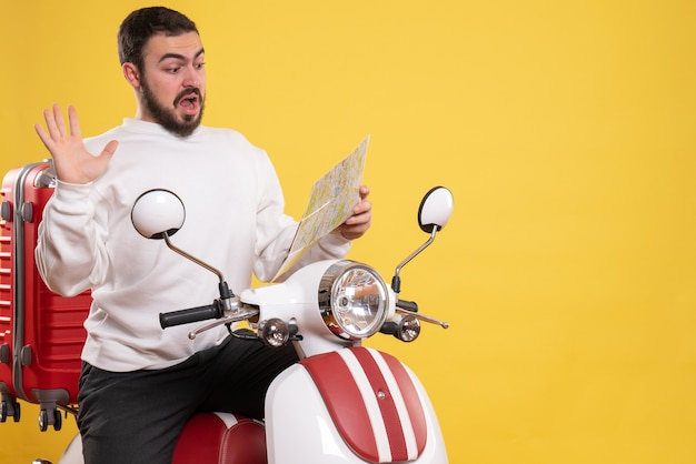 Front view of concerned man sitting on motorcycle with suitcase on it holding map on isolated yellow background