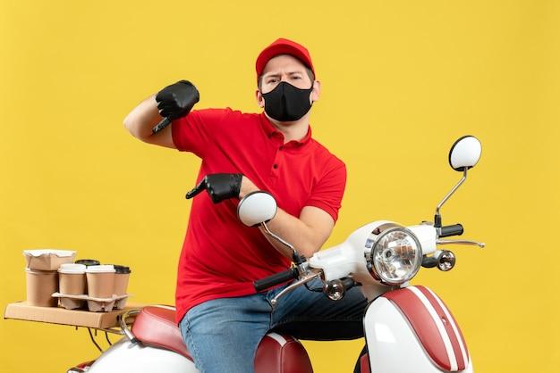 Vista frontale del giovane adulto interessato che indossa la camicetta rossa e guanti del cappello nella mascherina medica che trasporta l'ordine che si siede sul motorino su fondo giallo