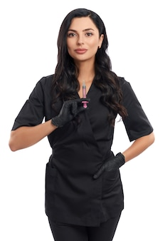 Front view of confident cosmetologist while standing on white with syringe in hands