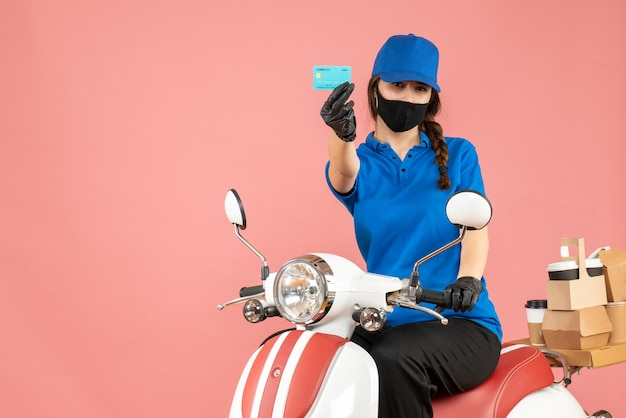 Front view of confident courier girl wearing medical mask and gloves sitting on scooter holding bank card delivering orders on pastel peach background
