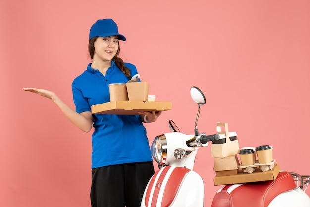 Vista frontale della signora del corriere fiduciosa in piedi accanto alla moto con in mano caffè e piccole torte su sfondo color pesca pastello