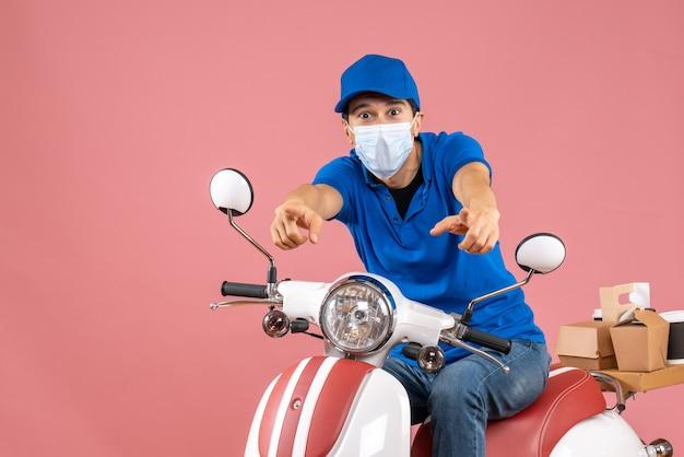 Vista frontale del corriere fiducioso in maschera medica che indossa cappello seduto su scooter su sfondo pesca pastello peach