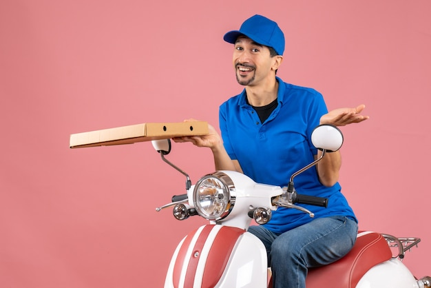Front view of confident courier man wearing hat sitting on scooter holding order on pastel peach background