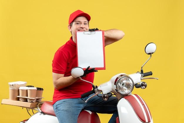 Vista frontale dell'uomo fiducioso del corriere che indossa guanti rossi della camicetta e del cappello nella mascherina medica che trasporta l'ordine che si siede sul documento della tenuta dello scooter
