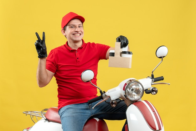 Vista frontale del corriere fiducioso uomo che indossa camicetta rossa e guanti cappello in maschera medica consegna ordine seduto su scooter tenendo gli ordini facendo gesto di vittoria