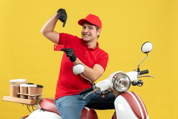 Vista frontale dell'uomo fiducioso del corriere che indossa guanti rossi della camicetta e del cappello nella mascherina medica che trasporta l'ordine che si siede sullo scooter che mostra la carta di credito