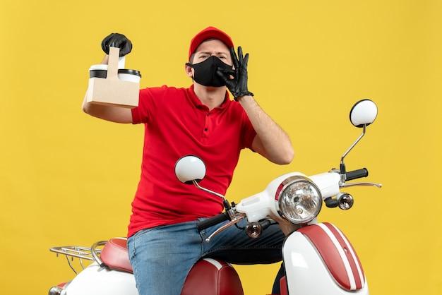 Vista frontale dell'uomo fiducioso del corriere che indossa guanti rossi della camicetta e del cappello nella mascherina medica che si siede sugli ordini della tenuta dello scooter che fanno gesto giusto