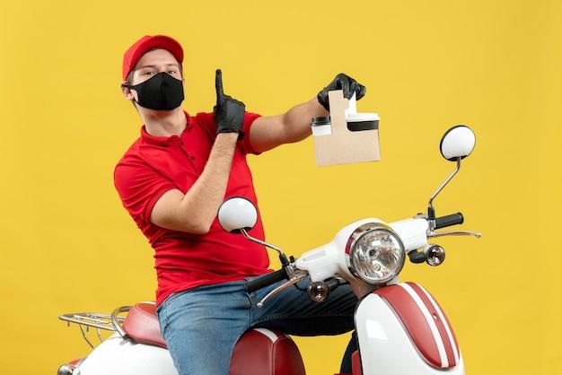 Vista frontale dell'uomo fiducioso del corriere che indossa guanti rossi della camicetta e del cappello nella mascherina medica che si siede sugli ordini della tenuta dello scooter che mostrano uno