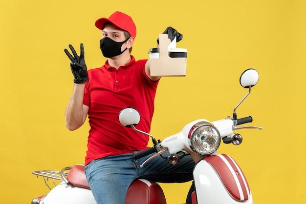 Vista frontale dell'uomo fiducioso del corriere che indossa guanti rossi della camicetta e del cappello nella mascherina medica che si siede sugli ordini della tenuta dello scooter che mostrano tre