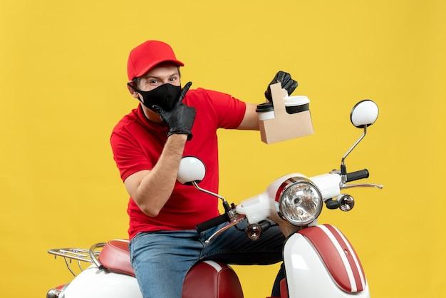 Vista frontale del corriere fiducioso uomo che indossa camicia rossa e guanti cappello in maschera medica seduto su uno scooter che mostra gli ordini