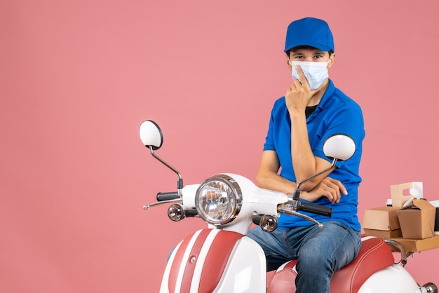 Front view of confident delivery guy in medical mask wearing hat sitting on scooter on pastel peach background