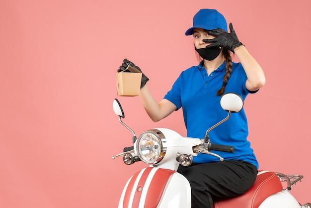 Vista frontale del fattorino fiducioso che indossa maschera medica e guanti seduto su uno scooter che consegna ordini su sfondo color pesca pastello