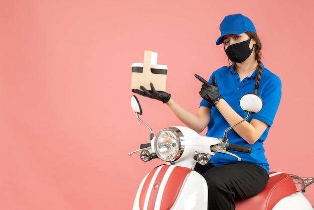 Vista frontale della donna sicura di consegna donna che indossa maschera medica e guanti seduto su scooter che consegna ordini su sfondo pesca pastello