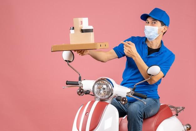 Vista frontale del fattorino maschio fiducioso in maschera con cappello seduto su scooter che consegna ordini su sfondo pesca pastello