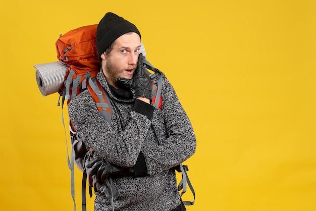 Vista frontale di un escursionista maschio fiducioso con guanti di pelle e zaino mettendo la mano sul mento