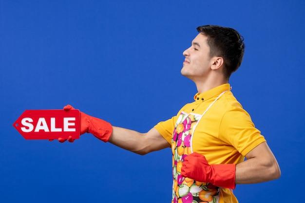 青いスペースに販売サインを保持している黄色のtシャツで自信を持って男性の家政婦の正面図