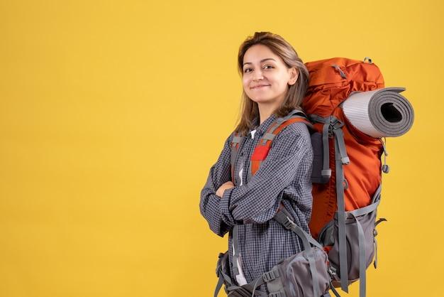 Vista frontale della donna viaggiatore fiducioso con le mani incrociate zaino rosso
