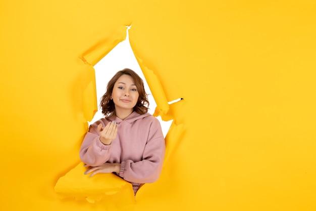 Vista frontale della donna sicura che chiama qualcuno e spazio libero sul giallo strappato