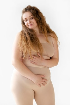 Front view of confident woman posing while wearing a body shaper
