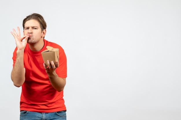 Vista frontale del giovane ragazzo fiducioso in camicetta rossa che tiene piccola scatola che fa gesto perfetto su priorità bassa bianca
