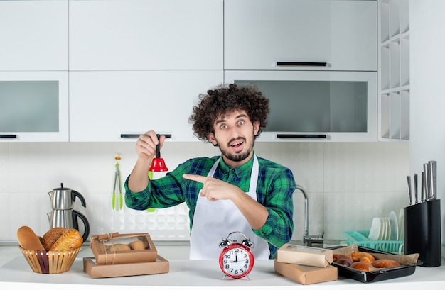 Front view of confident young man standing behind the table various pastries on it and holding red ring bell in the white kitchen