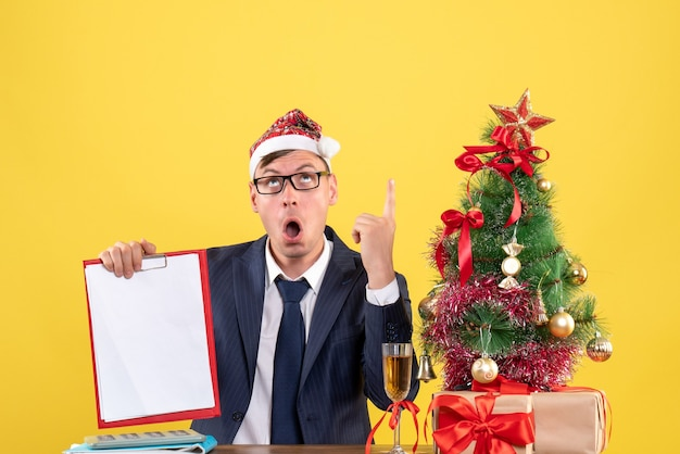 Front view of confused business man holding clipboard sitting at the table near xmas tree and presents on yellow