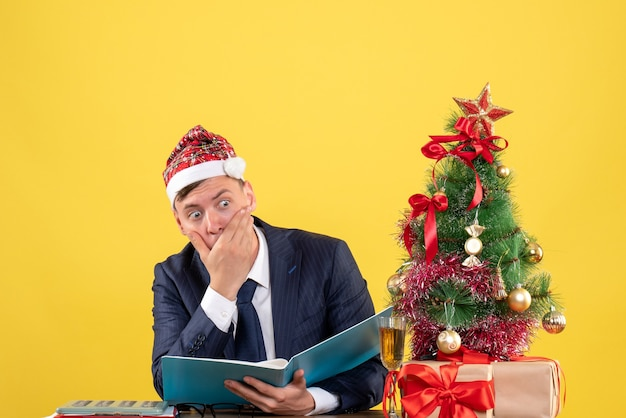 Front view of confused business man sitting at the table near xmas tree and presents on yellow