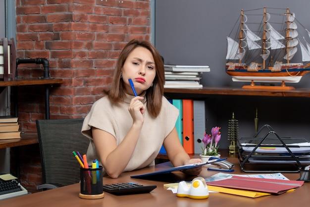 사무실에서 책상에 앉아 카메라를 보고 혼란 비즈니스 여자 전면 보기