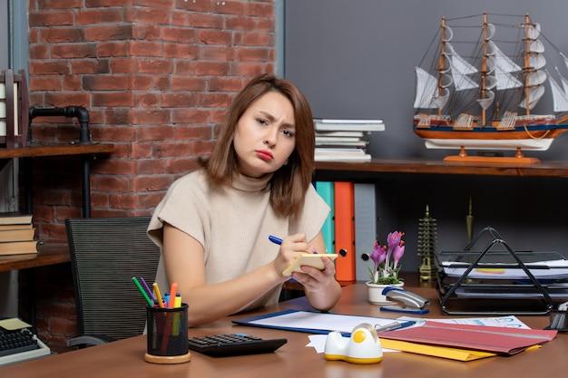 Donna d'affari confusa vista frontale che prende appunti seduta alla scrivania in ufficio