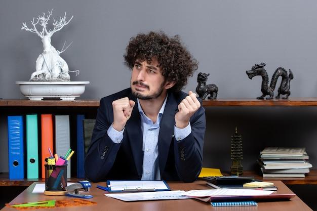 Вид спереди сбитый с толку бизнесмен, сидящий за столом