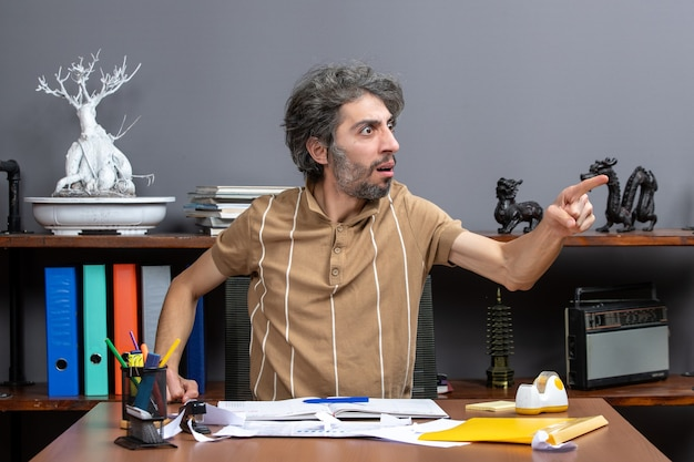 Front view confused businessman sitting at desk in his office pointing at right