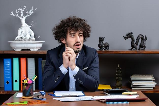 Vista frontale uomo d'affari confuso seduto alla scrivania nel suo ufficio