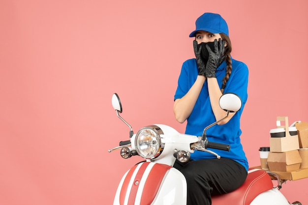 Front view of confused courier girl wearing medical mask and gloves sitting on scooter delivering orders on pastel peach background