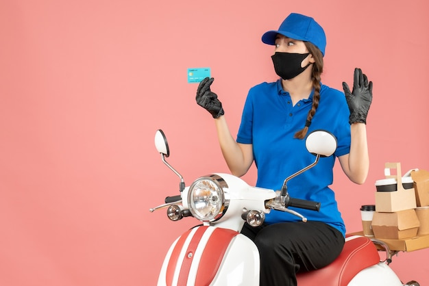 Front view of confused courier girl wearing medical mask and gloves sitting on scooter holding bank card delivering orders on pastel peach background