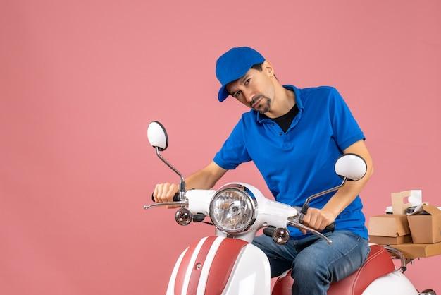 Vista frontale del corriere confuso che indossa un cappello seduto su uno scooter su sfondo color pesca pastello