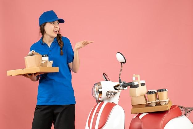 Vista frontale della signora corriere confusa in piedi accanto alla moto con in mano caffè e piccole torte su sfondo color pesca pastello