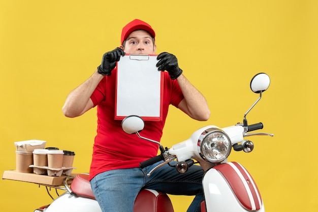 Vista frontale dell'uomo confuso del corriere che indossa guanti rossi della camicetta e del cappello nella mascherina medica che consegna l'ordine che si siede sul documento della tenuta dello scooter
