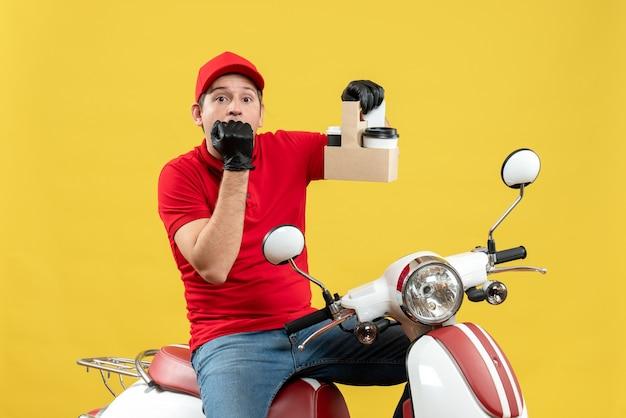Vista frontale dell'uomo confuso del corriere che indossa guanti rossi della camicetta e del cappello nella mascherina medica che consegna l'ordine che si siede sugli ordini della tenuta dello scooter