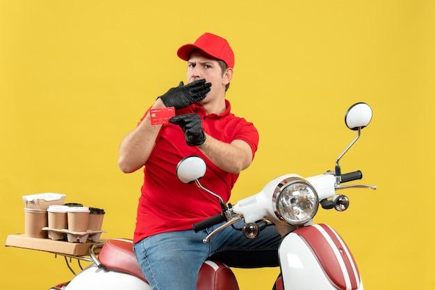 Vista frontale dell'uomo confuso del corriere che indossa guanti rossi della camicetta e del cappello nella mascherina medica che consegna l'ordine che si siede sullo scooter che mostra la carta di credito