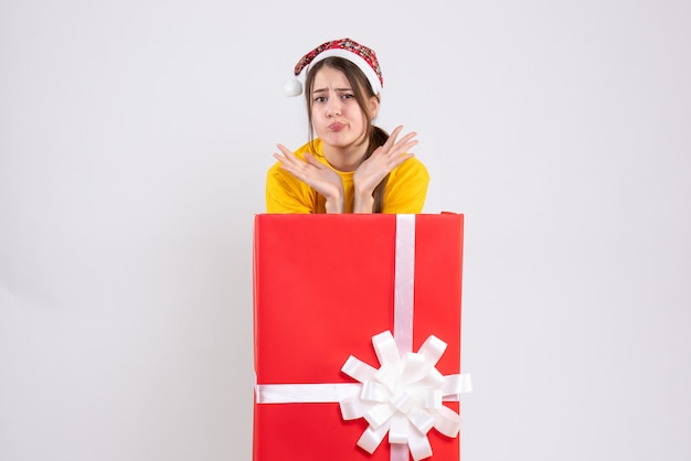Front view confused cute girl with santa hat standing behind big xmas gift