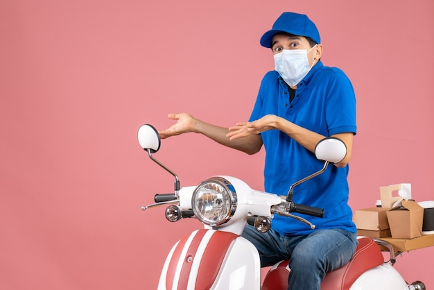 Front view of confused delivery guy in medical mask wearing hat sitting on scooter on pastel peach background