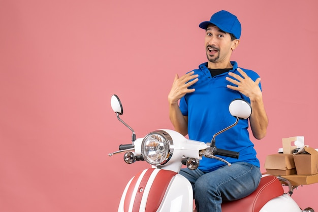 Front view of confused delivery guy wearing hat sitting on scooter pointing himself on pastel peach background