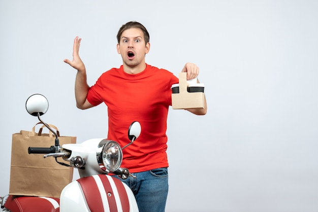 Vista frontale dell'uomo di consegna confuso in uniforme rossa che sta vicino al motorino che mostra ordine su fondo bianco