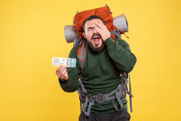 Front view of confused emotional traveller guy with backpack showing ticket on yellow background