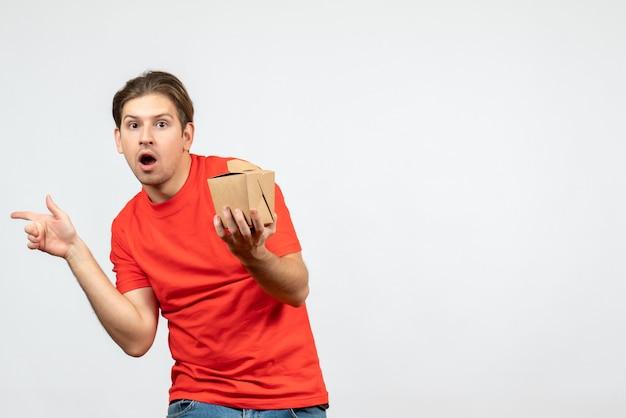 Vista frontale del giovane ragazzo emotivo confuso in camicetta rossa che tiene piccola scatola che indica qualcosa sul lato destro su priorità bassa bianca