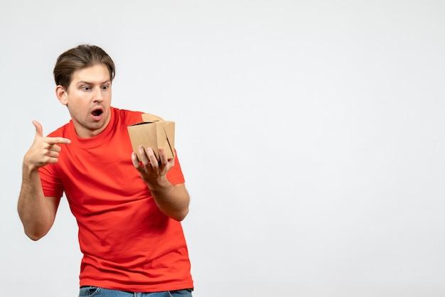 Vista frontale del giovane ragazzo emotivo confuso in camicetta rossa che indica piccola scatola su priorità bassa bianca