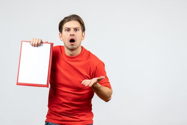 Vista frontale del giovane emotivo confuso in camicetta rossa che tiene documento su priorità bassa bianca